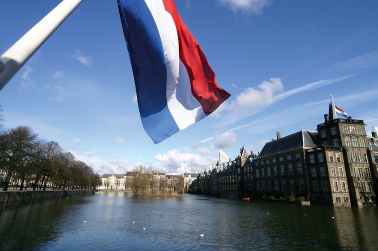 Dutch flag with the parliament buildings in the background